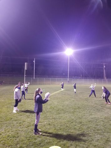 Softball team practicing while social distancing and wearing masks.